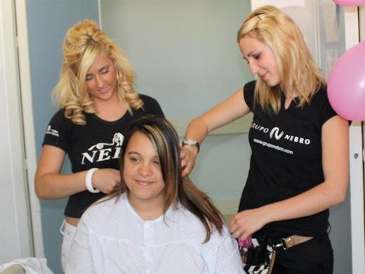 Dos peluqueras en formación peinan a una paciente